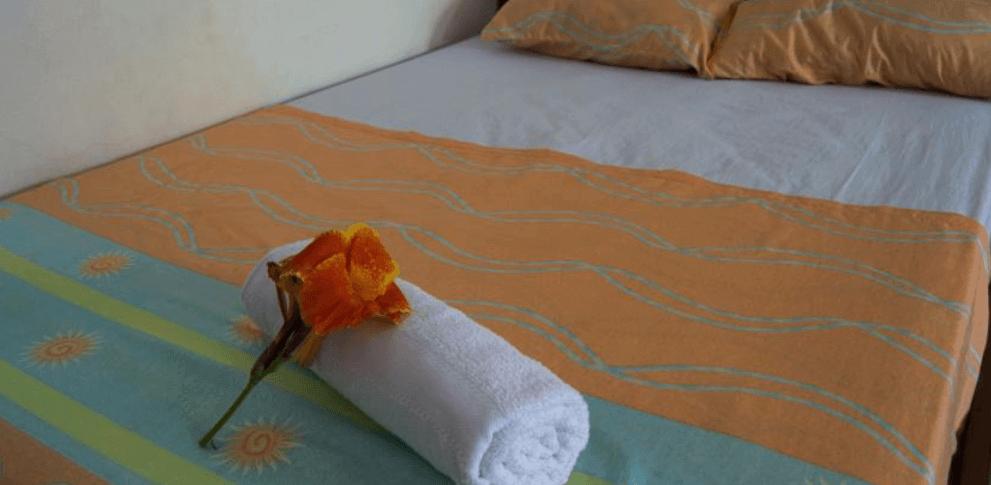 Fotografía de una cama con un paño y flores encima